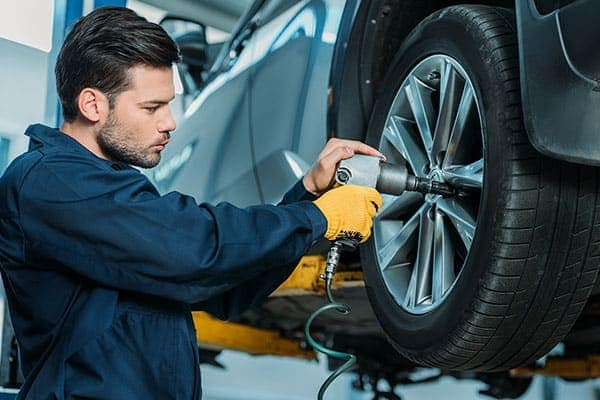 Man with gelled makes a seductive face while he attaches or removes a tire from a vehicle.