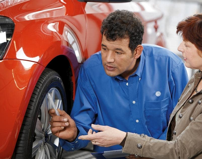 Volkswagen technician points something out on a tire to a woman with red hair.