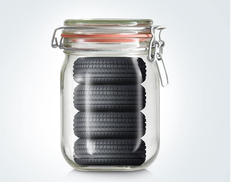 Four tiny tires in a mason jar. Or, four regularly-sized tires in a giant mason jar. The tire are being stored, is the intention. of this image.