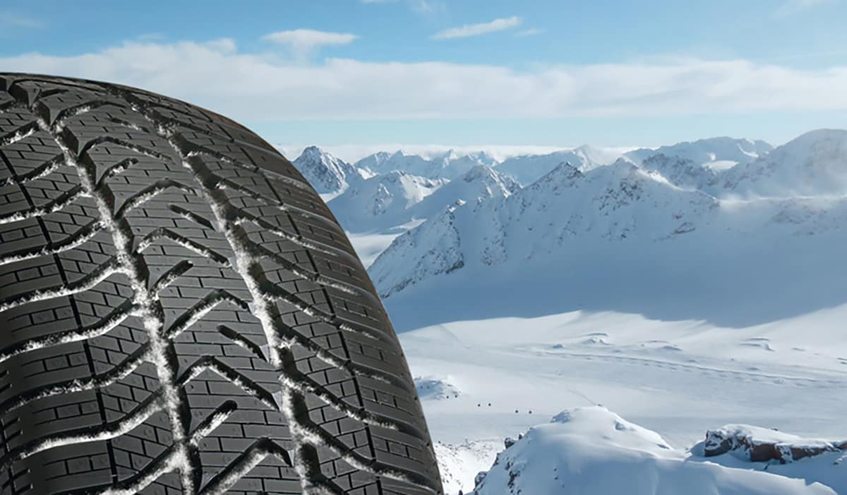 A Volkswagen winter tire rests atop a mountain and surveys a frozen landscape.