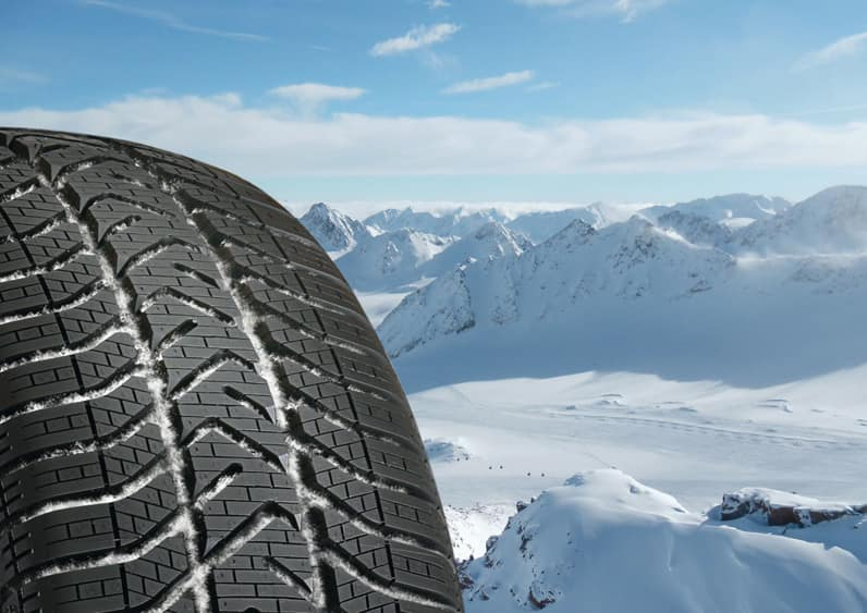 A Volkswagen winter tire stands on a mountain and surveys a frozen landscape.