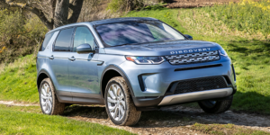 Light blue Discovery sport on dirt and grass road with trees around it