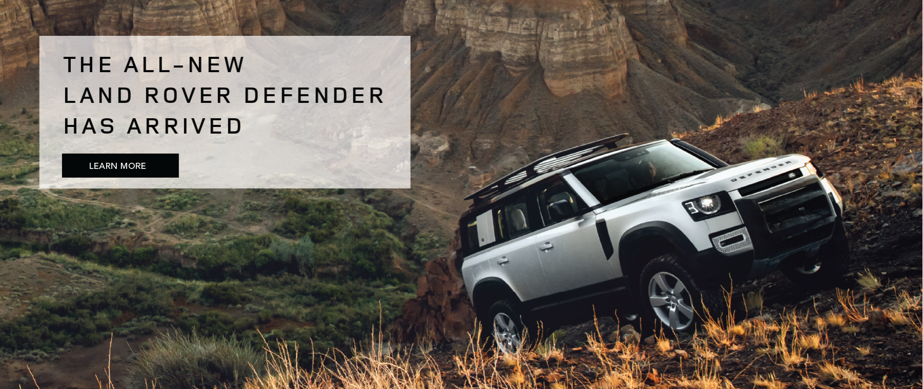 LAND ROVER DEFENDER DRIVING UP MOUNTAIN ON ON ROCKY TERRAIN WITH TREE COVERED VALLEY BELOW. THE ALL-NEW LAND ROVER DEFENDER HAS ARRIVED. LEARN MORE.
