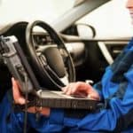 Mechanic checks the power steering of the vehicle with his cars only computer device