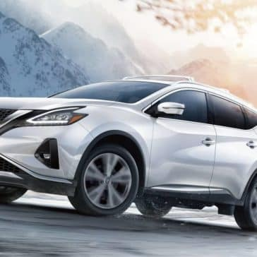 White 2019 Nissan Murano driving up snowy mountain with sun glare