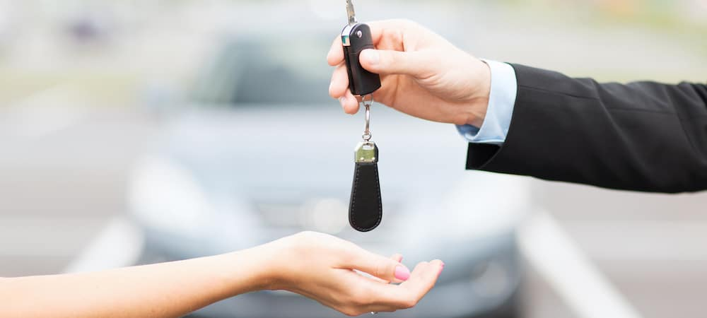 Car dealer handing over car keys to woman with car in background