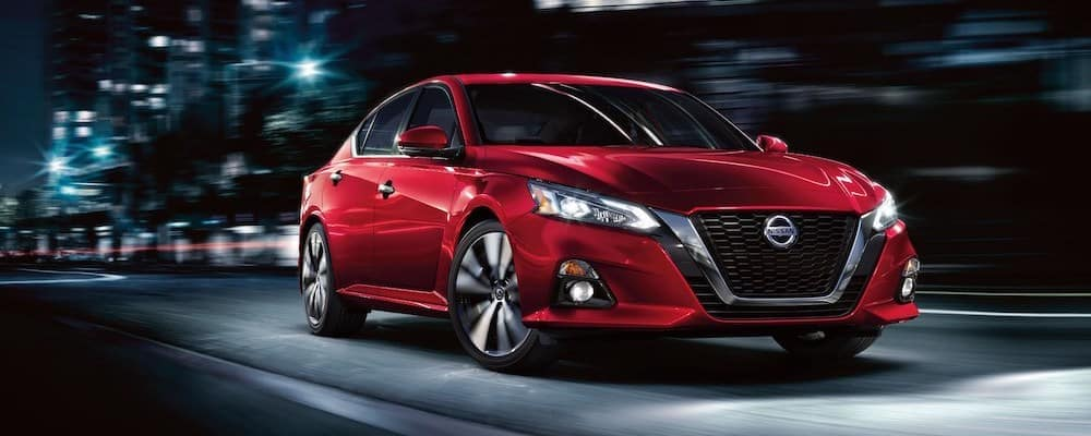 Red 2020 Nissan Altima on city street at night