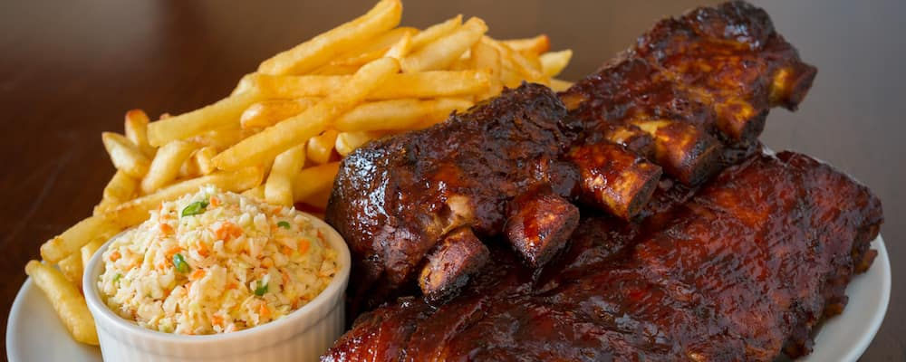 A delicious-looking rack of ribs sits next to a small dish of cole slaw, and some french fries.