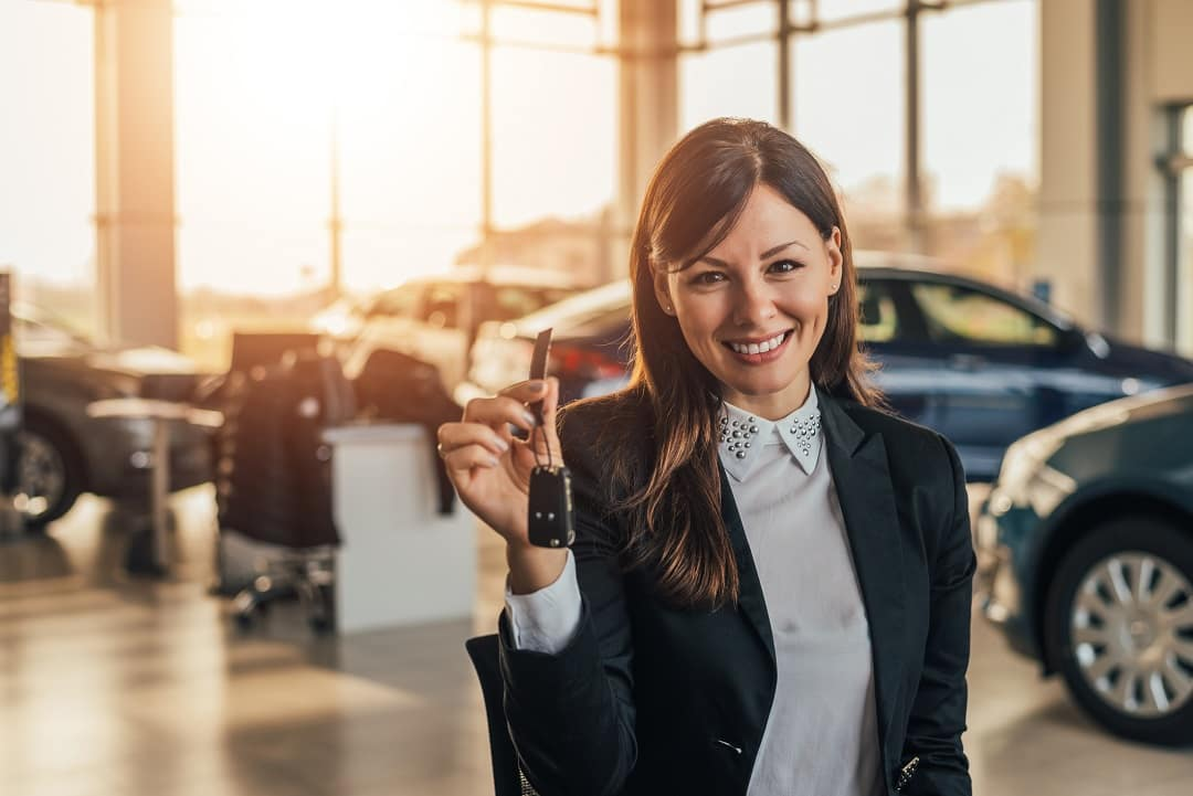 Cheerful young woman showing her new car key at dealership Killen, TX.