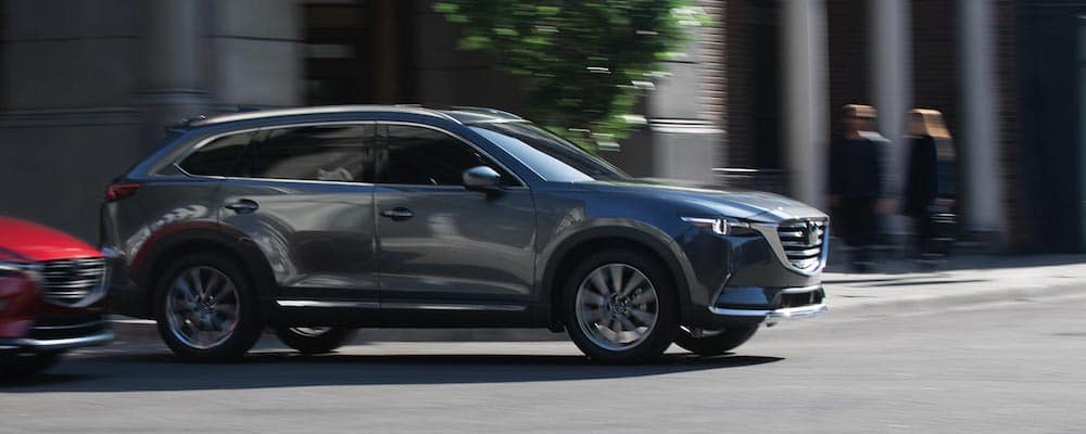 dark colored 2019 mazda cx-9 driving on city street