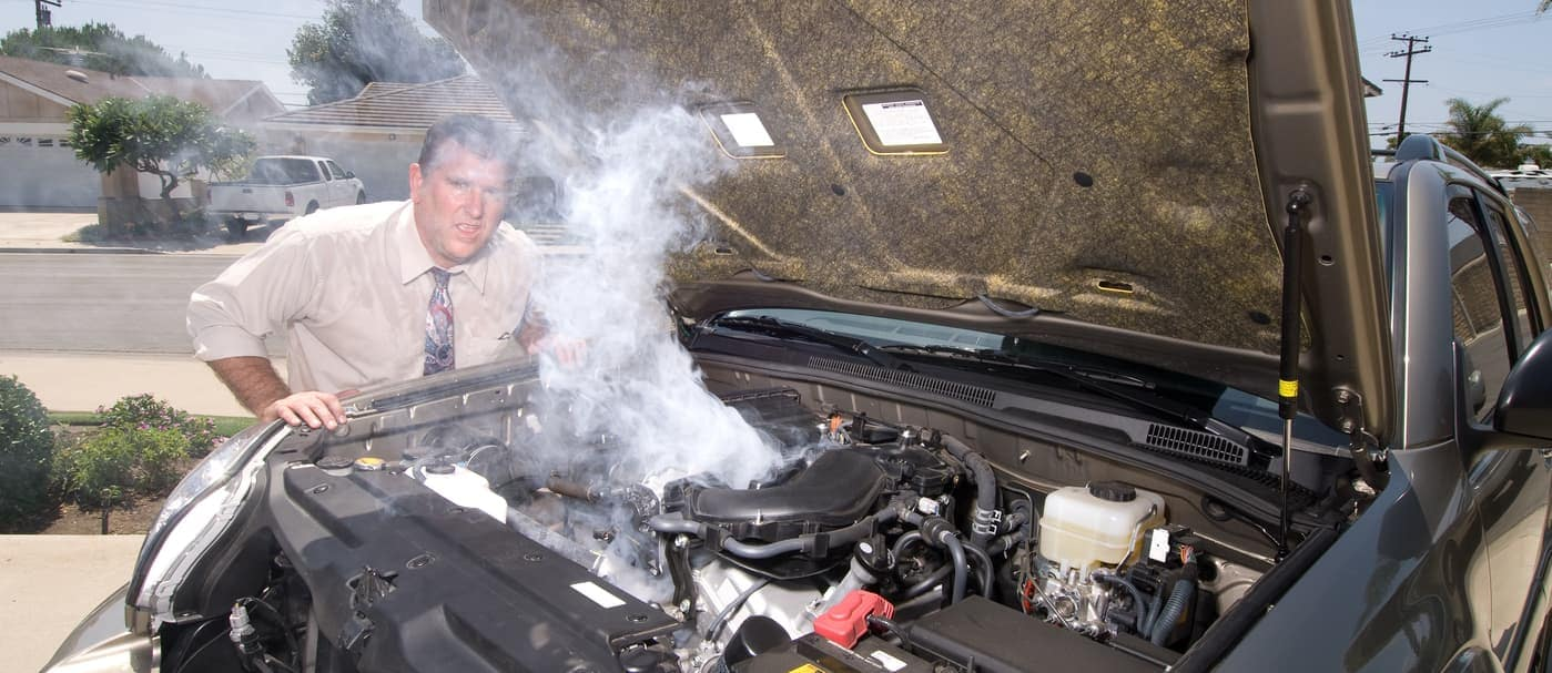 man upset in front of overheating car