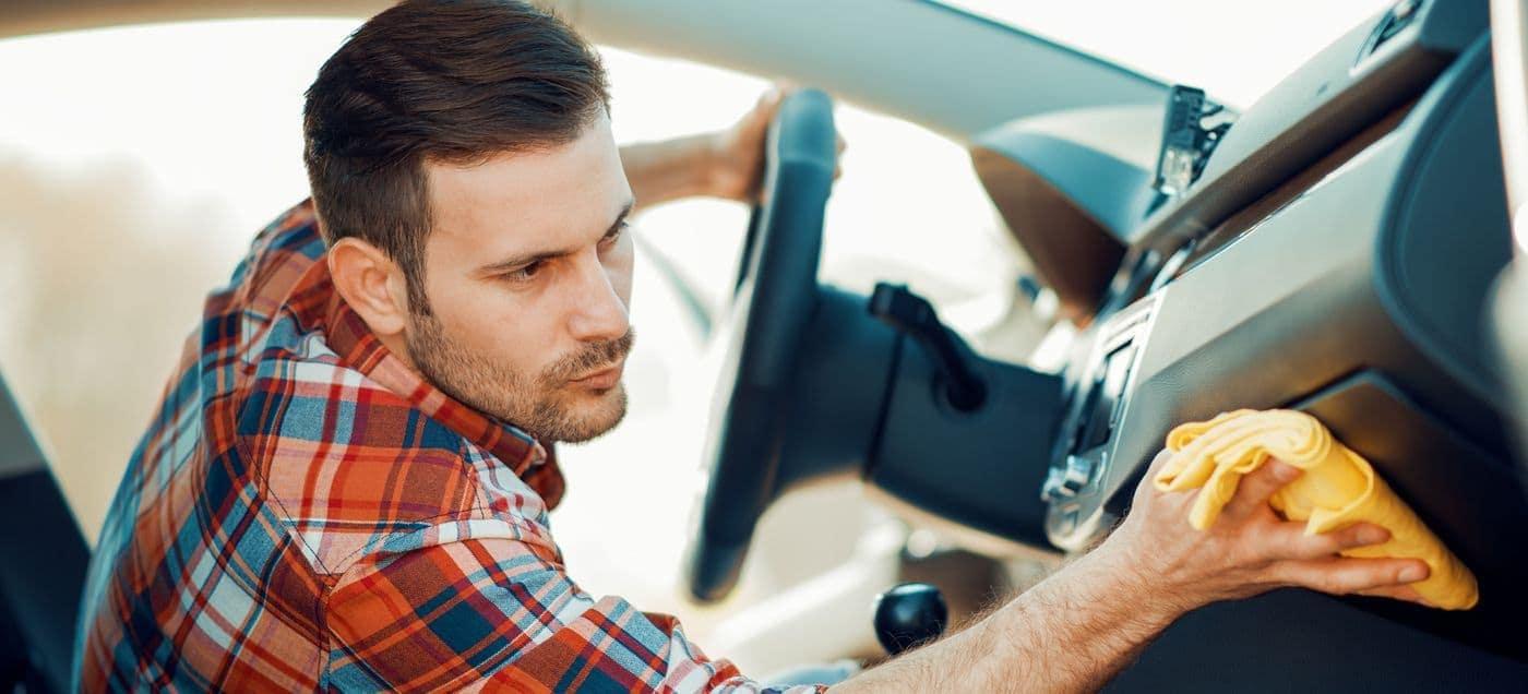 man sanitizing inside of vehicle