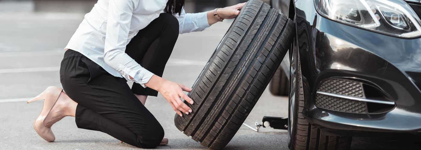 Woman putting on spare tire
