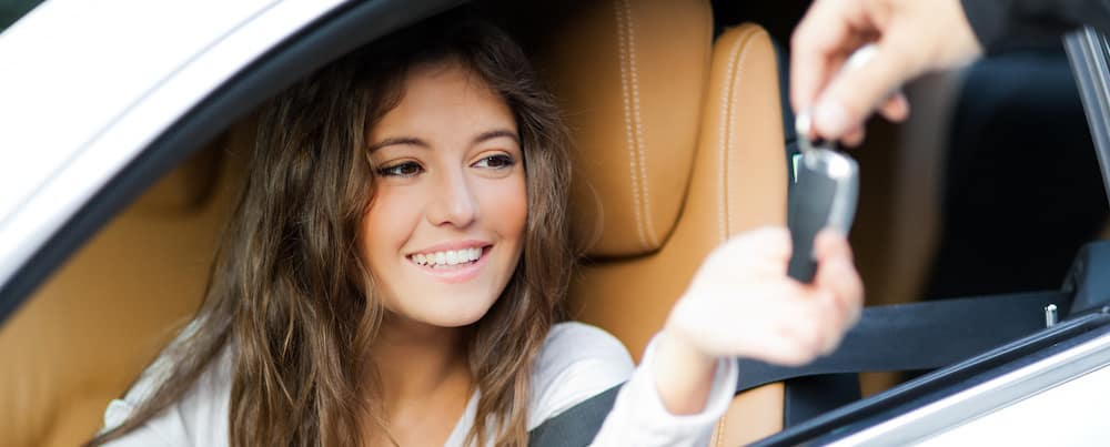 woman in car smiling while being handed car keys