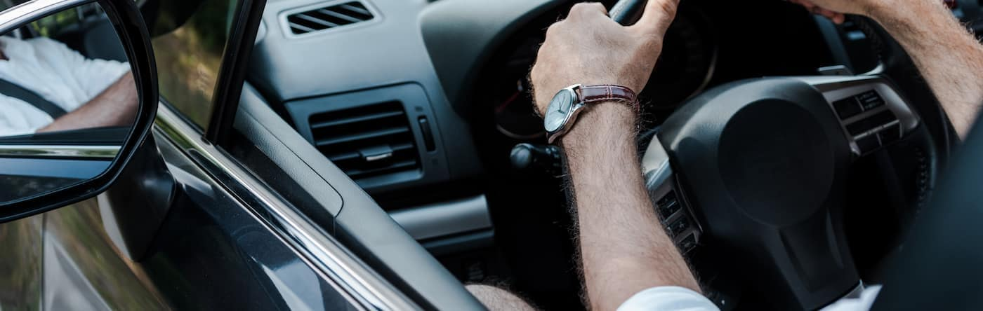 man driving with hands on the steering wheel