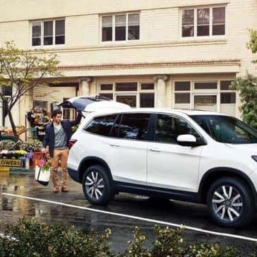 Man loading groceries into cargo area of 2019 Honda Pilot