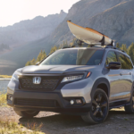 2021 honda passport silver exterior parked outside by a scenic body of water