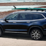 2021 honda pilot blue exterior parked on beach with board on roof