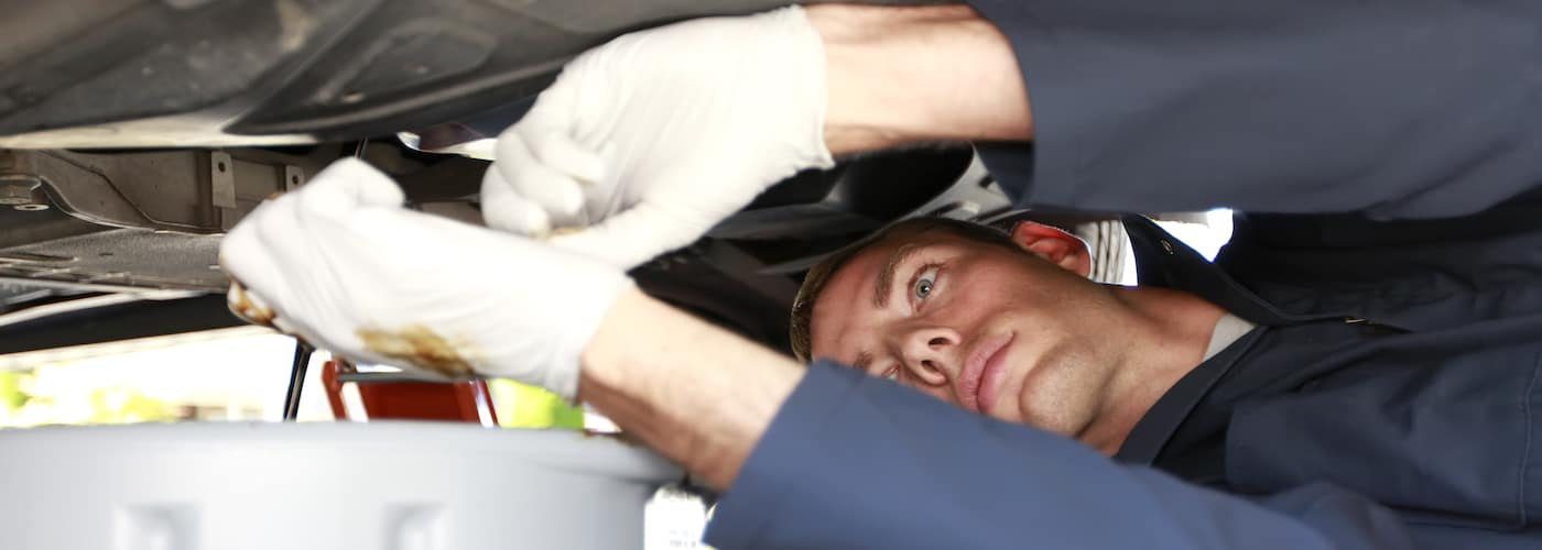 close up of mechanic changing oil under car