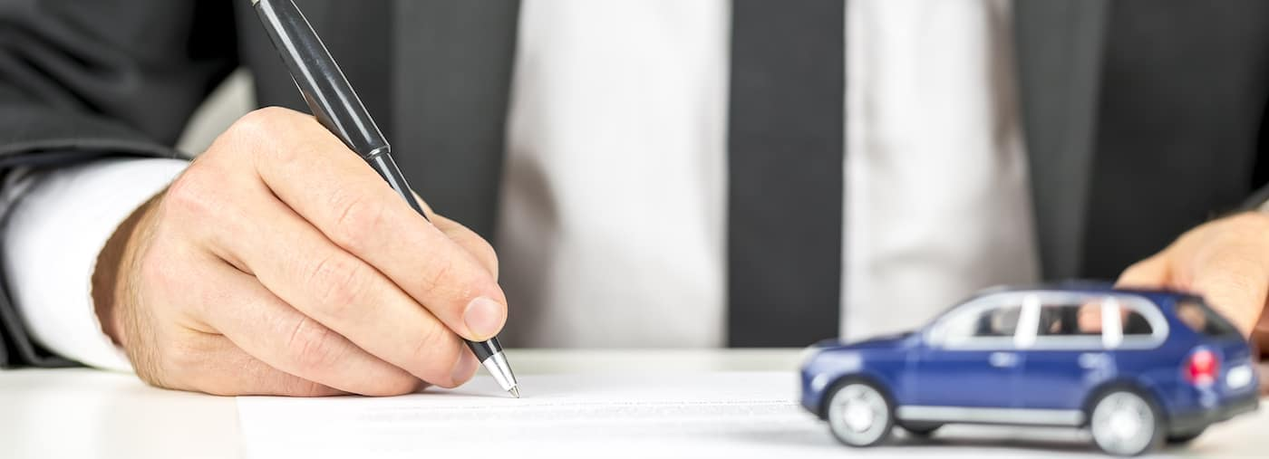 Car financing paperwork with little blue car