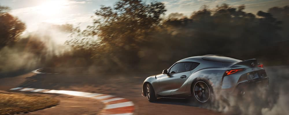 A 2020 Toyota Supra drifts around a corner while the sun shines down on the track.