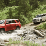 two toyota 4runner models off-roading in forest