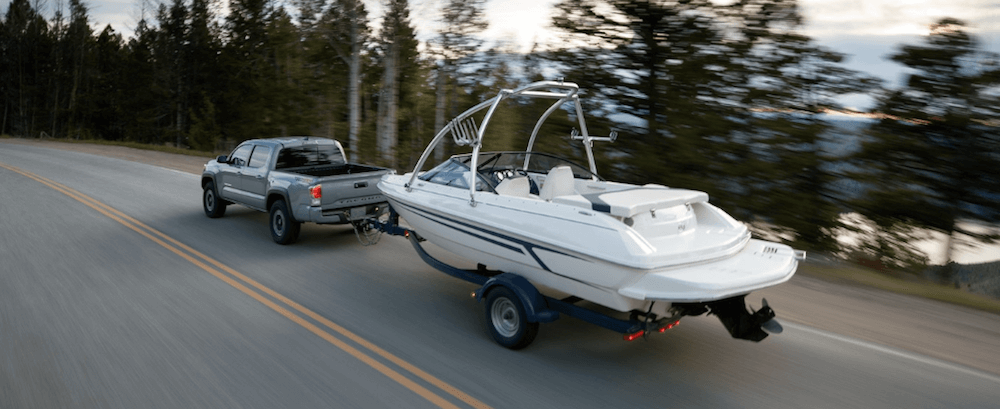 2020 Toyota Tacoma towing boat on highway