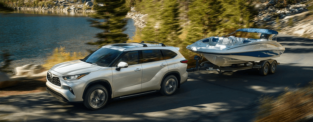 2020 Toyota Highlander towing boat on lakeside road