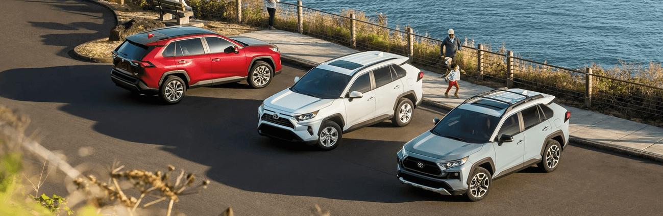 2020 Toyota RAV4 in blue, red, and white near beachside