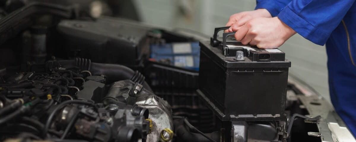 service technician replacing a car battery