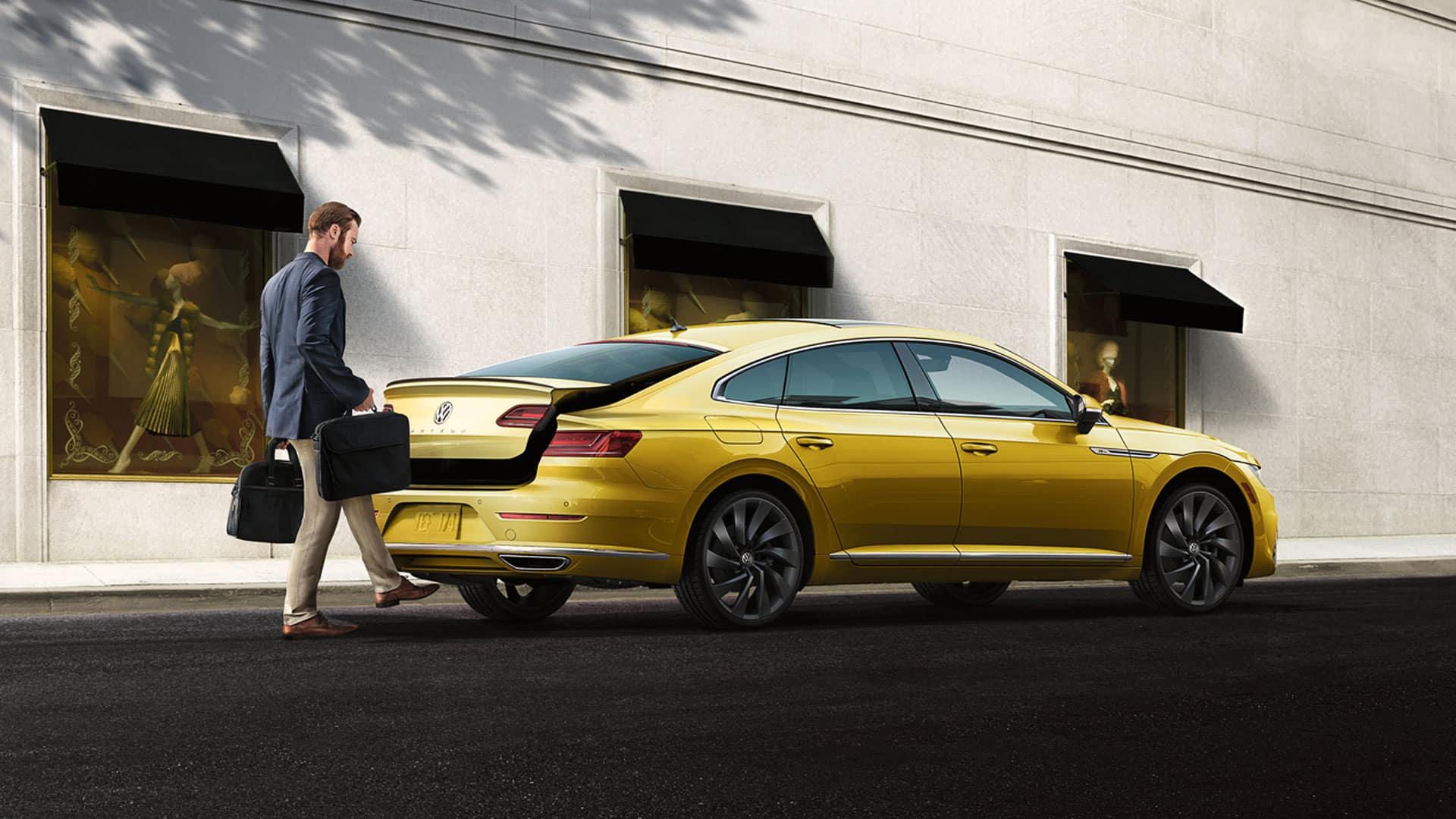 Man with bags opening the trunk of a Gold Arteon