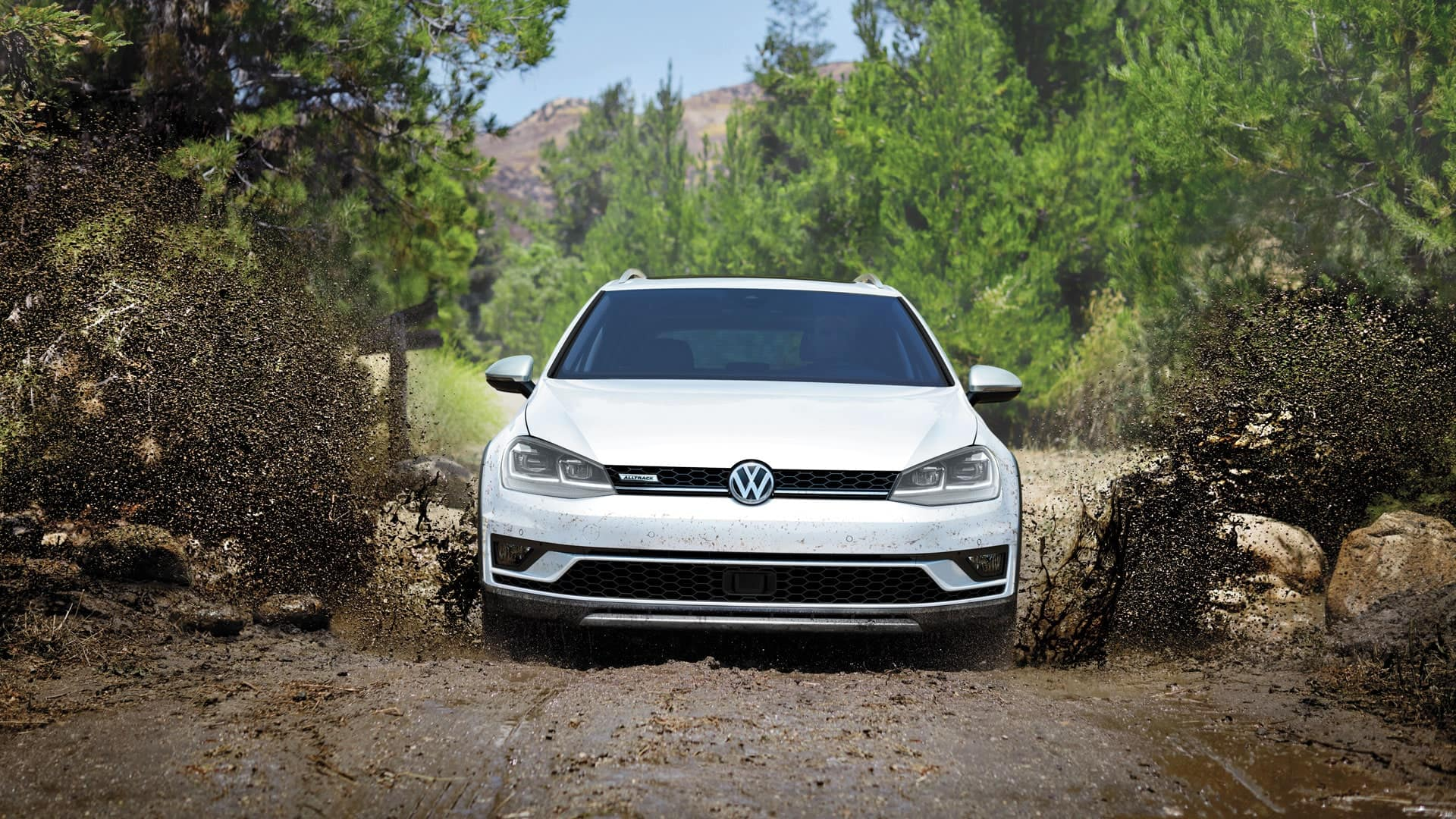 White 2019 VW Golf Alltrack offroading through a giant puddle of mud.