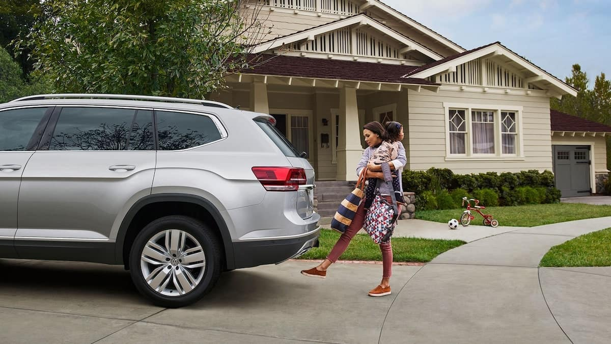 A woman hold a child and several bags takes advantage of the Power Liftgate feature of the Atlas.