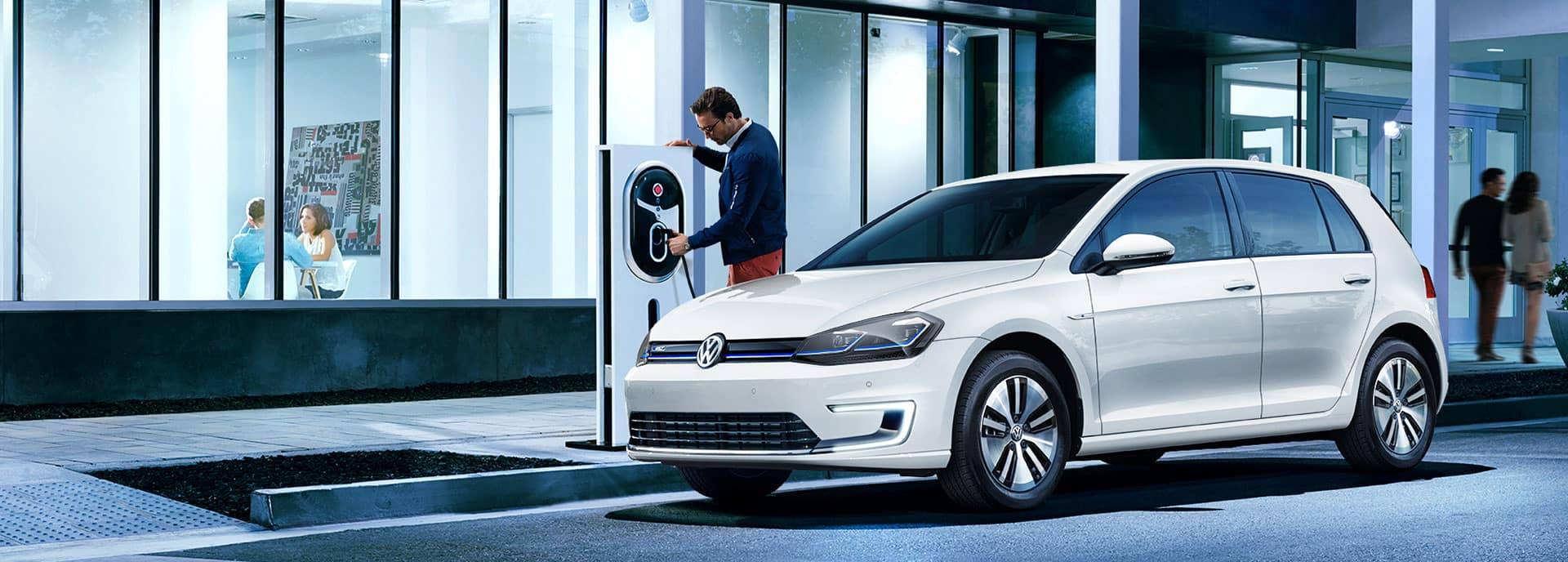 Man charging the 2019 VW e-Golf at a charging station