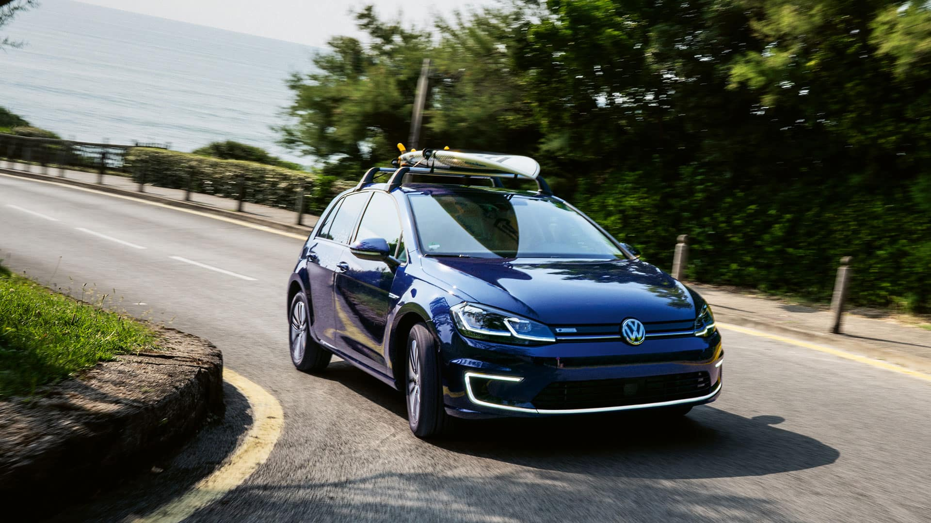 Blue 2019 VW e-Golf turning a corner. A surf board is on the roof rack.