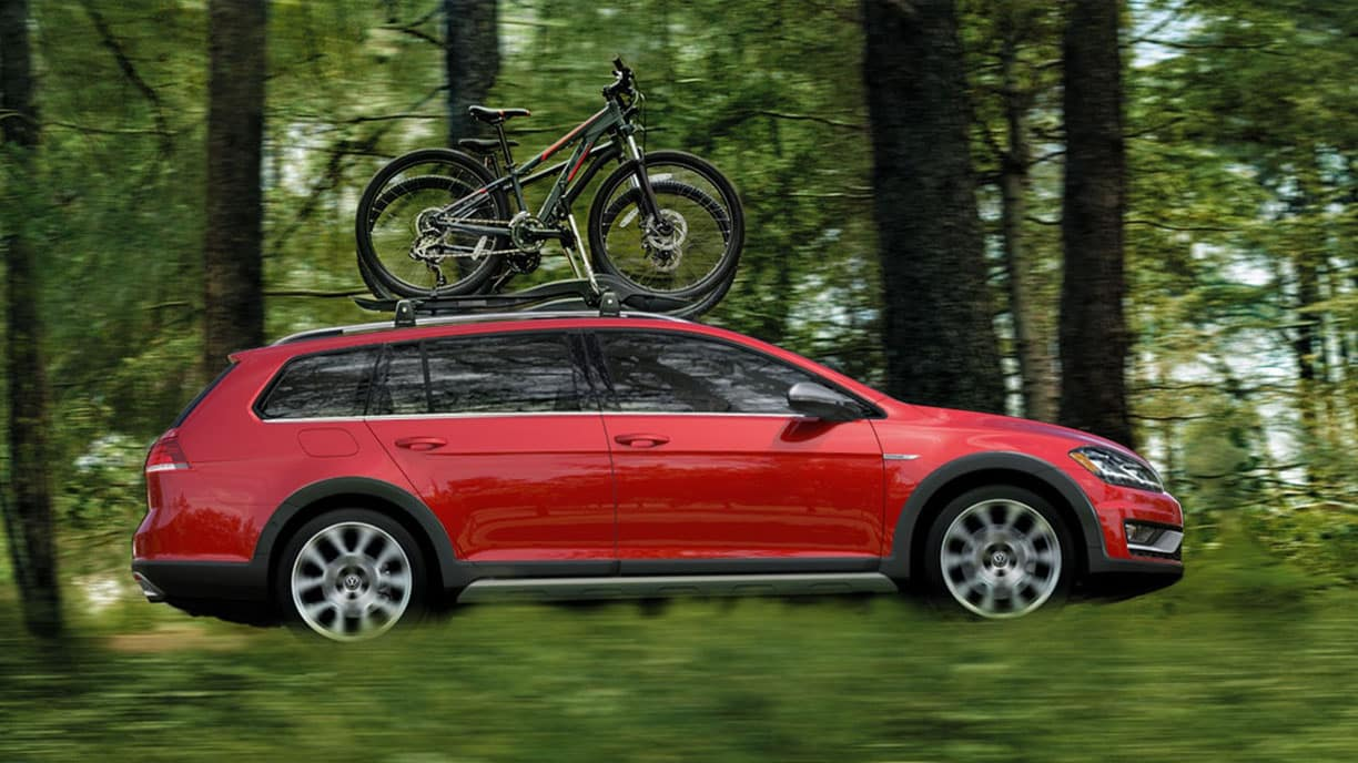 Red 2019 VW Golf Alltrack driving through a forest with bikes on the roof rack