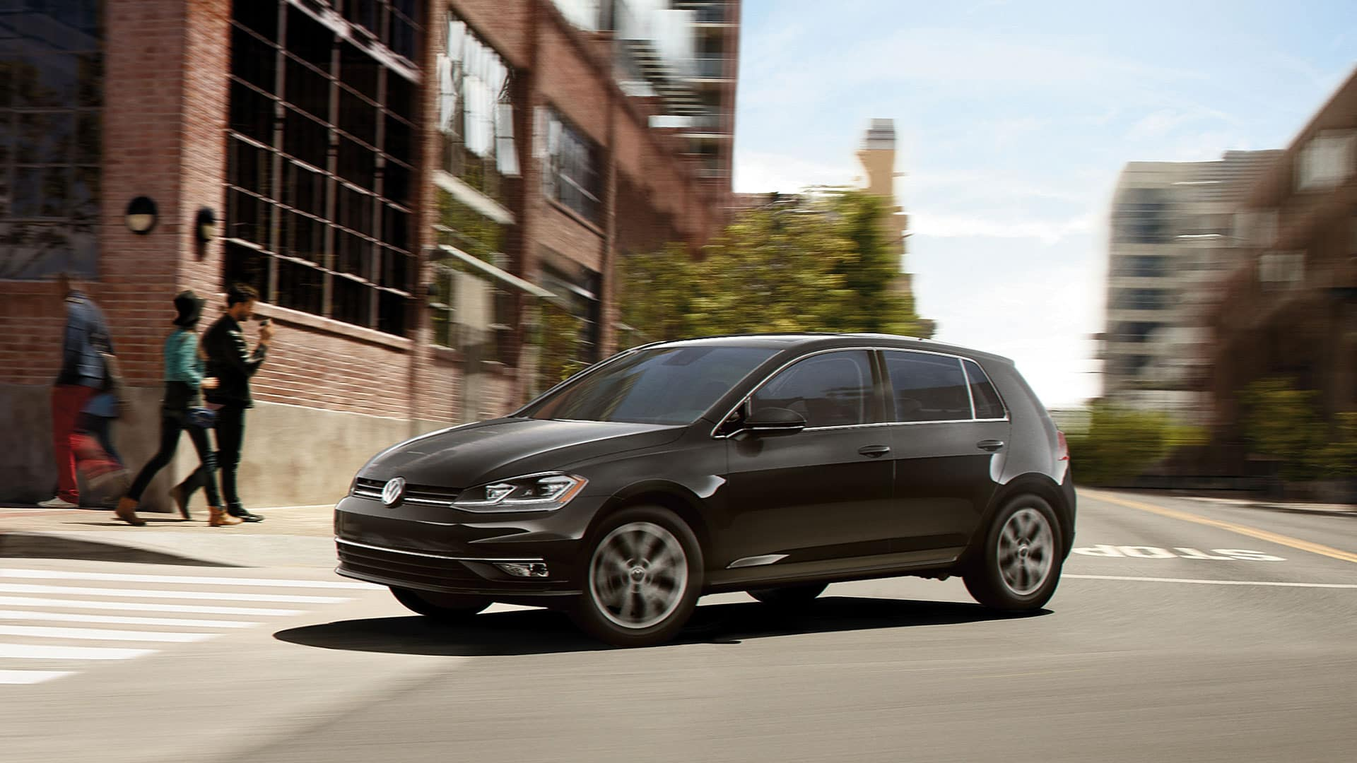 A black 2019 VW Golf showing off it's cross differential system to several hipsters outside an old factory that has been converted to office space or lofts.