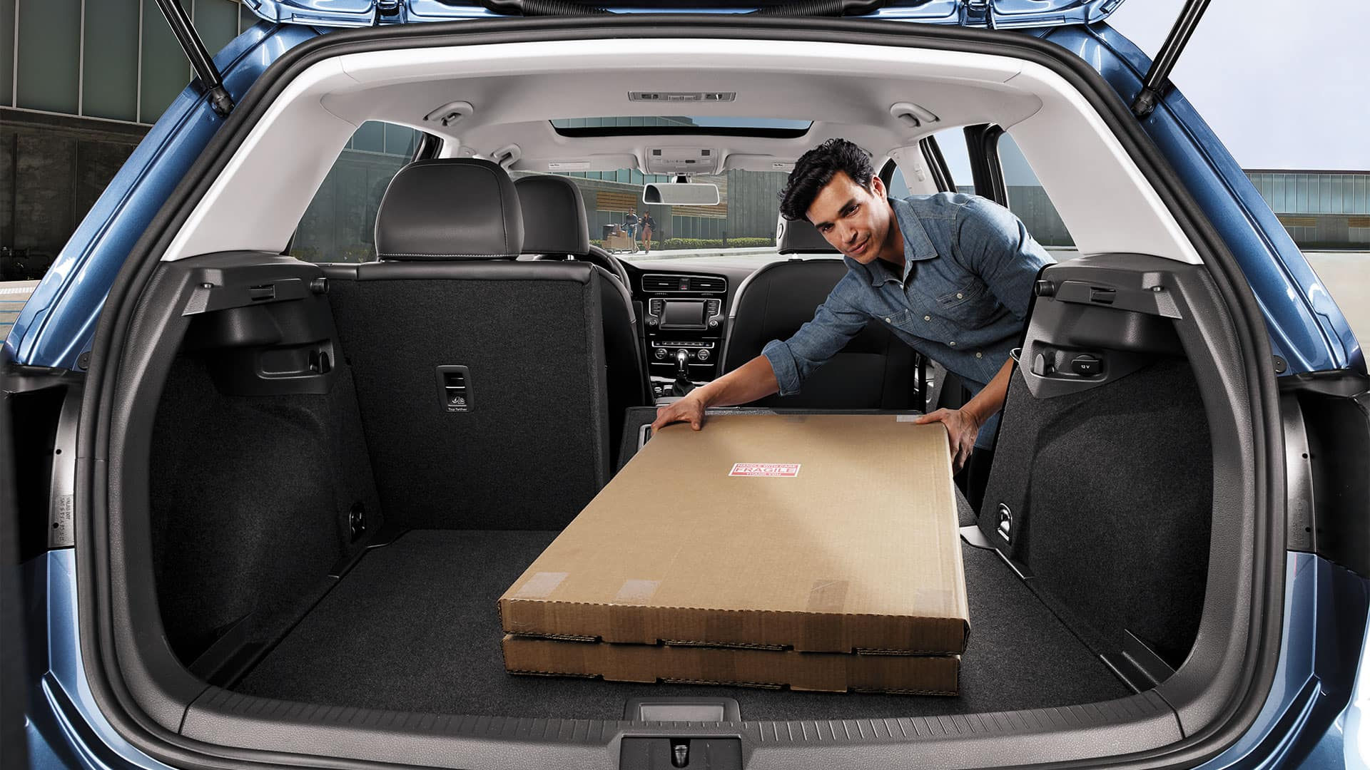 Man using the 2019 VW Golf folding seats feature to transport otherwise unwieldy boxes.