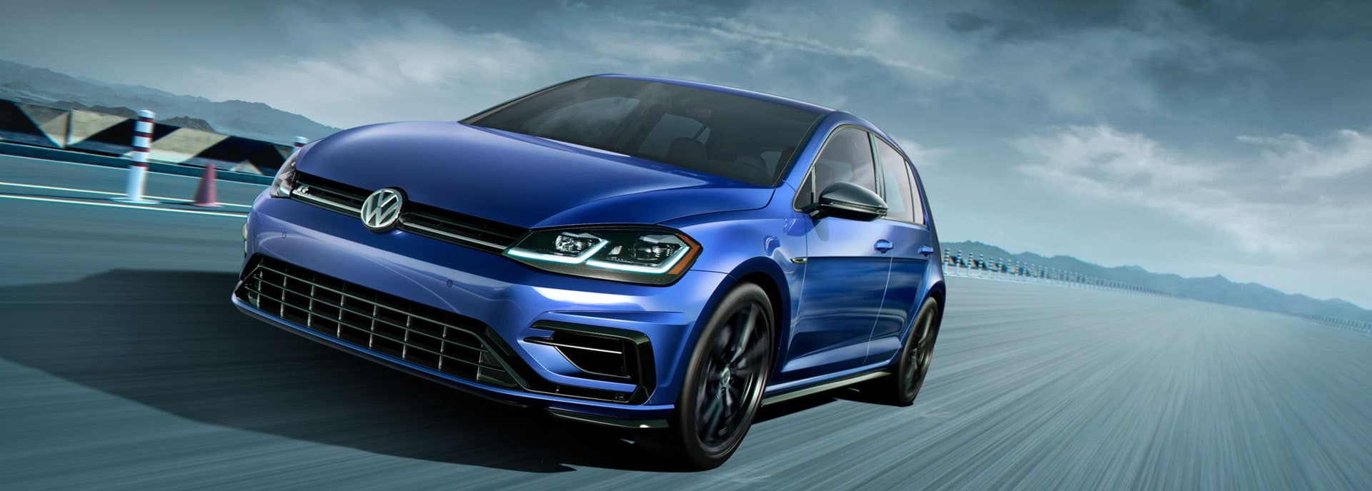 Dynamic photo of a blue 2019 VW Golf R on a race track