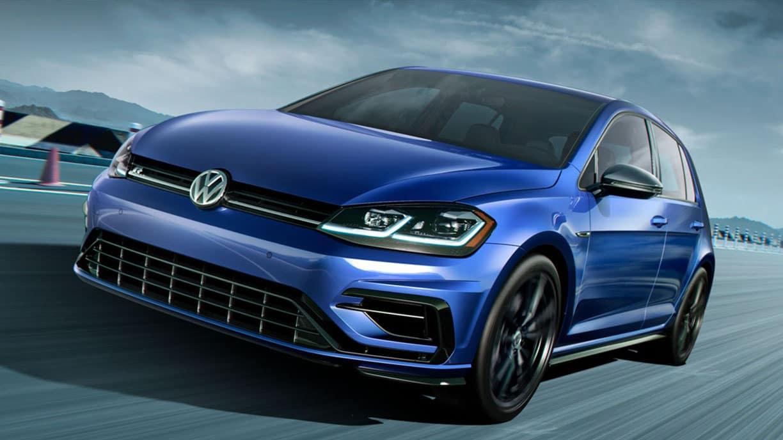 Dynamic photo of a blue 2019 VW Golf R on a race track