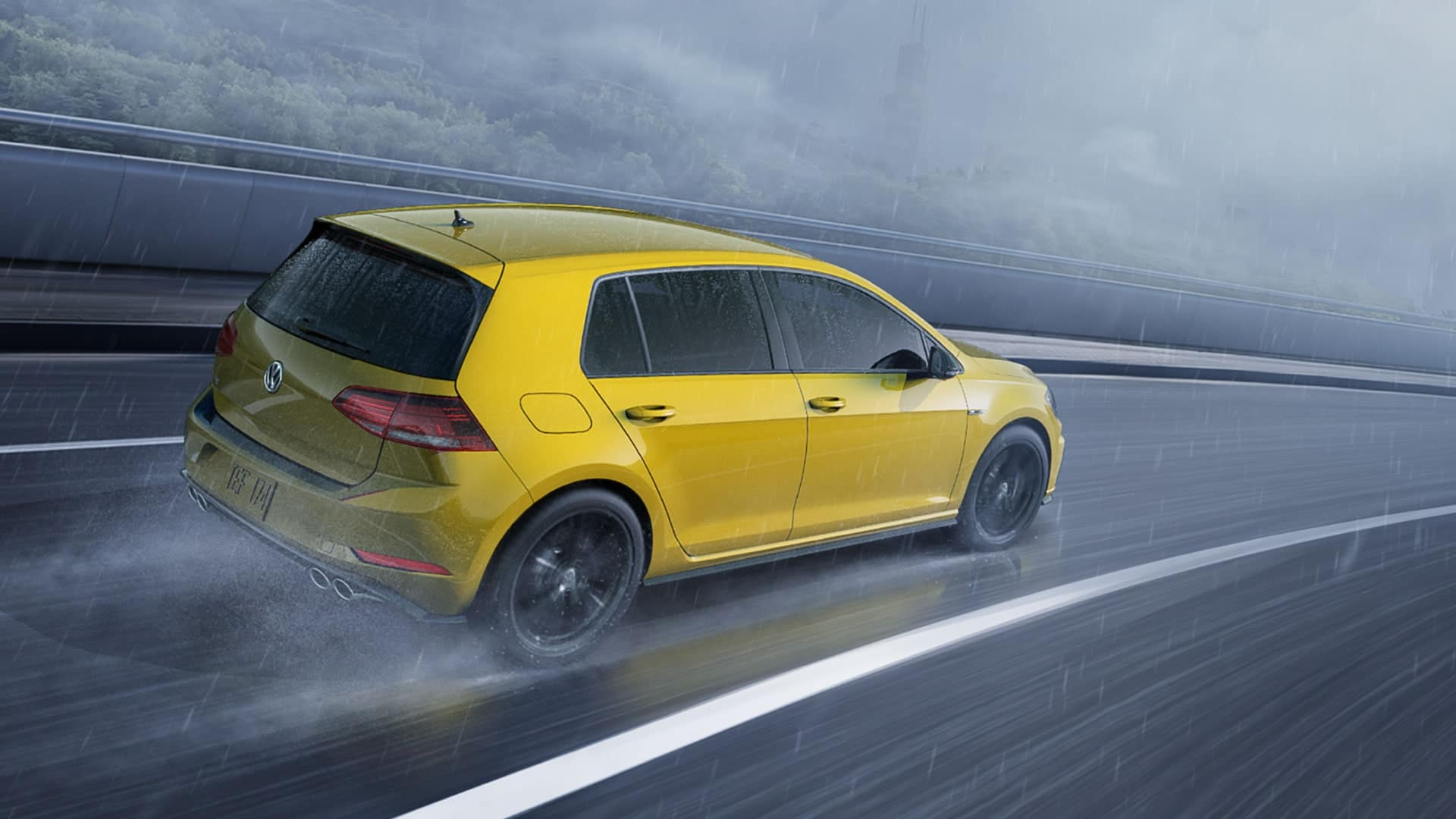 A yellow 2019 VW Golf R drives quickly and confidently through the rain.