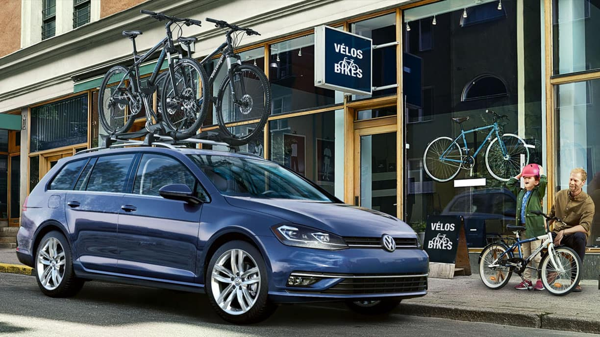 Blue 2019 VW Golf SportWagen with bikes on a roof rack