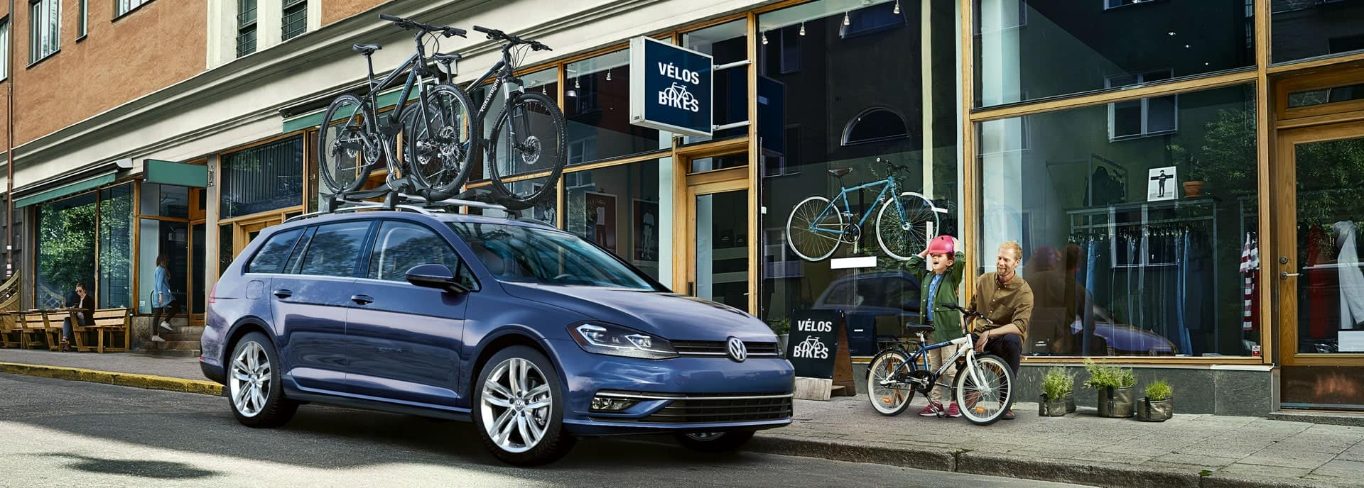 Blue 2019 Golf SportWagen at the bike shop. A little girl with a pink bicycle helmet is overjoyed. A man, presumably her father, seems happy but restrained.