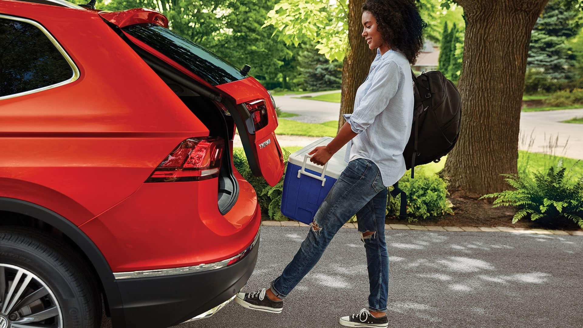 Woman with her hands full takes advantage fo the Tiguan's power liftgate by simply waving her foot under the rear bumper to open the rear door.