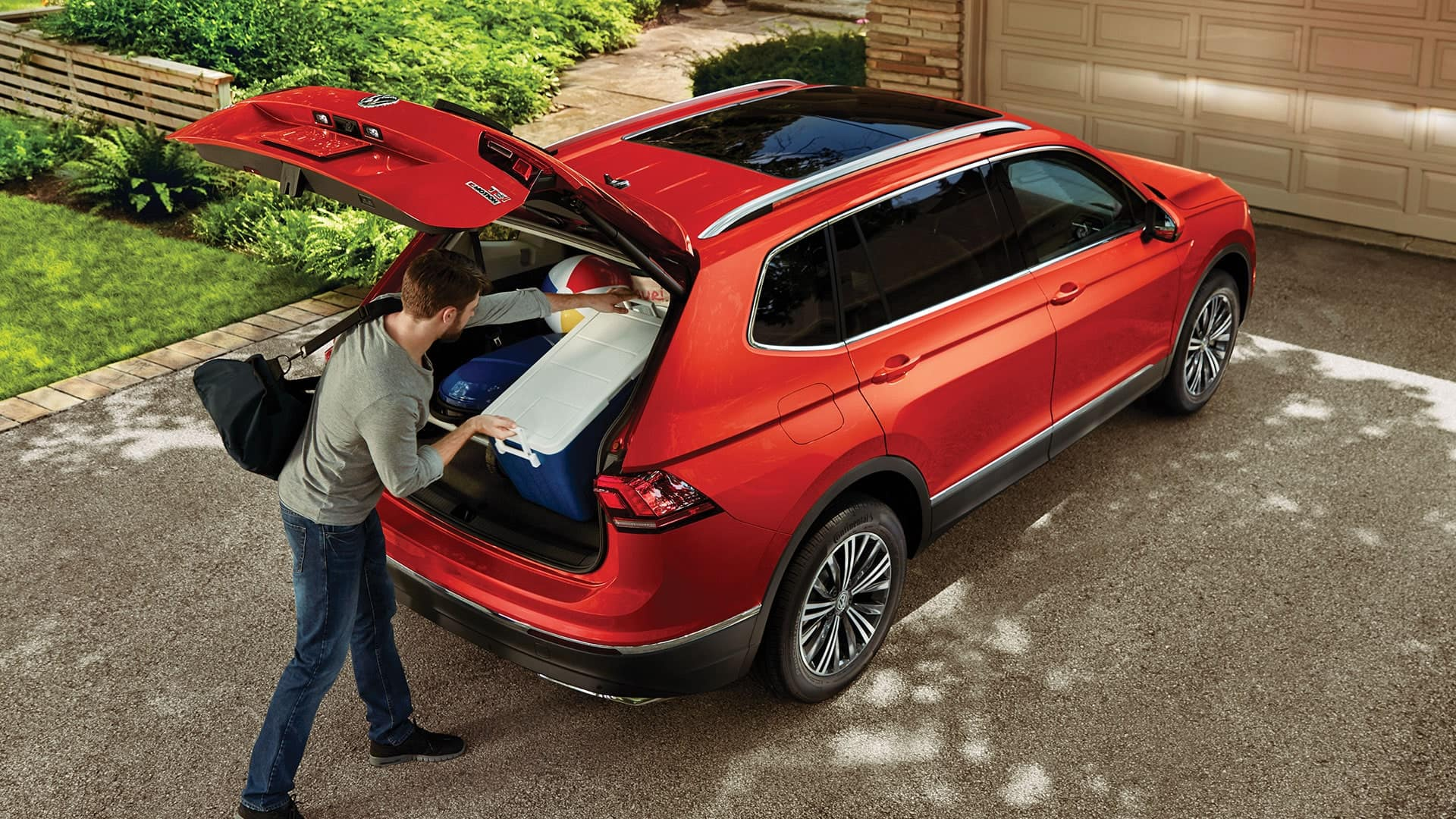 Man takes advantage of the spacious interior of the Tiguan to pack everything required for a beach barbecue.