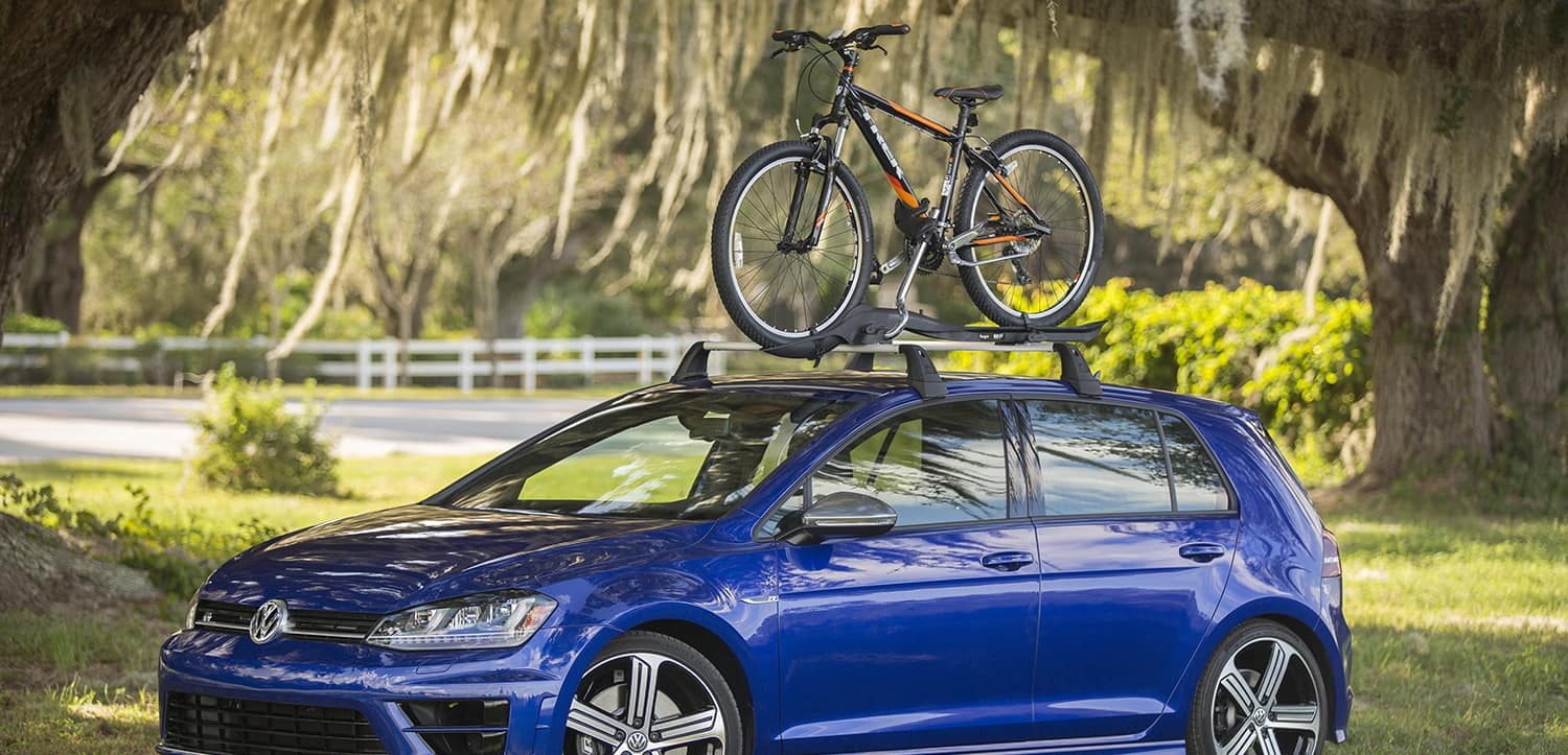 Blue Volkswagen Golf with a bike rack in a park.